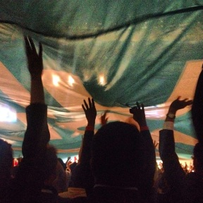 The crowd holding up an enormous One Young World flag